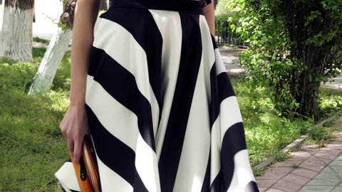 young woman in black white striped flared skirt holds mustard color clutch against green grass in park close view