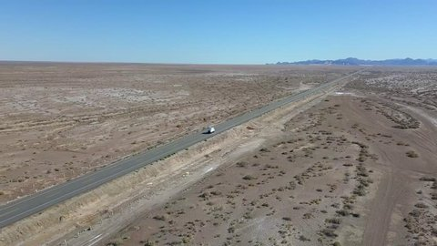 Drone view following a rv truck driving on a desert road, aerial shot, on a sunny day, in San Felipe, Baja, California, Mexico