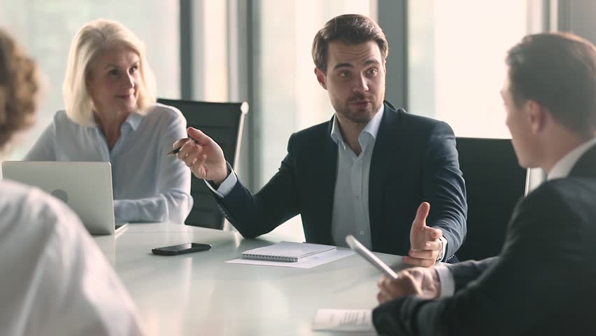 Businessman in suit talking to business people colleagues or partners sitting at conference table, male leader discussing work at team meeting or group negotiations having conversation with clients #1028099081