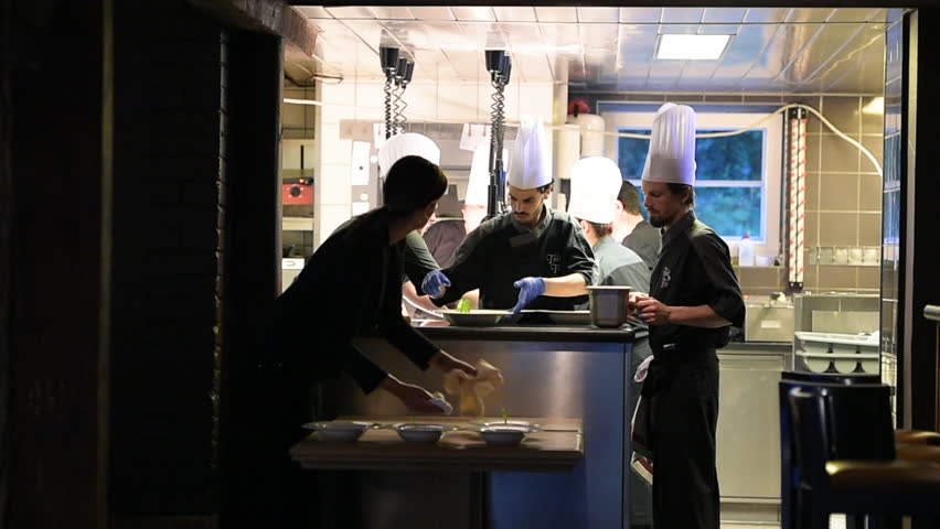 Paris, France - Circa 2019: Teamwork in restaurant - chef arranging multiple leaves on the dish plate inside cuisine as waiters takes dishes for the wedding, reception, official meeting reunion