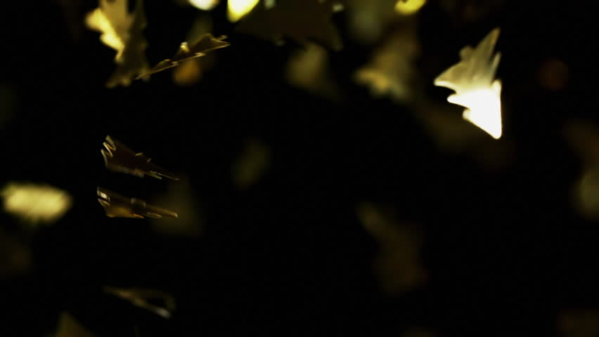 Golden christmas tree particles flying after being exploded, bright confetti bouncing against camera flying and falling down on black background. Top view close up macro slow motion | Shutterstock HD Video #1028119571
