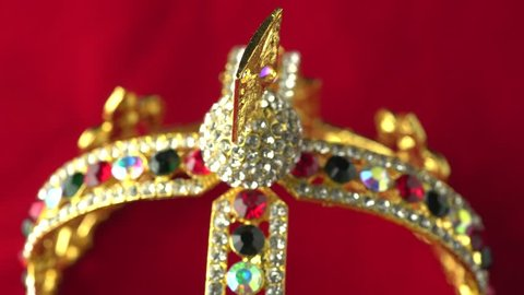 Gold diamond crown or decorative pageant accessory close up focus on the top. Slowly rotation on the red royal color surface. 4k, uhd.