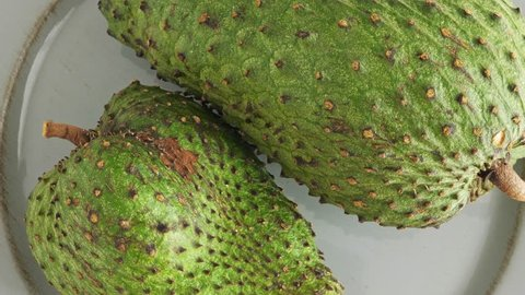 One soursop graviola, exotic, tropical fruit Guanabana on plate, Rotate