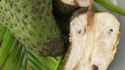 Closeup of green soursop graviola, exotic, tropical fruit Guanabana on plate, Rotate