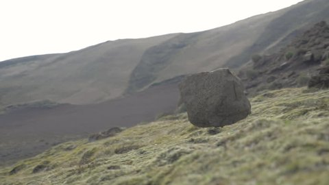 Big rock rolling down a steep hill in slow motion