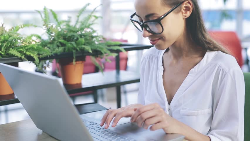 Concentrated young beautiful smiling businesswoman working on laptop in bright modern office. Business or freelance concept | Shutterstock HD Video #1028141291