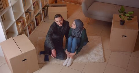 Closeup top shoot of young muslim couple sitting on the floor in a newly bought apartment smiling happily dreaming about how to furniture the room indoors