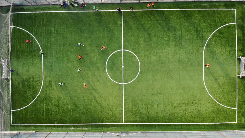 A group of children playing football on a new field with artificial turf. The player scores a goal against an opponent #1028258651