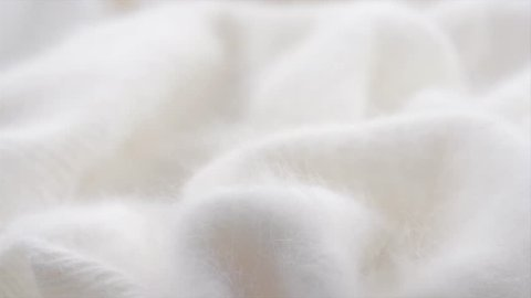 Soft Wool background. Alpaca wool mohair clothes texture closeup. Natural Cashmere Soft and fluffy merino wool macro shot. Woolen fabric. Knitted hairy detail texture surface Rotated. 4K UHD slowmo