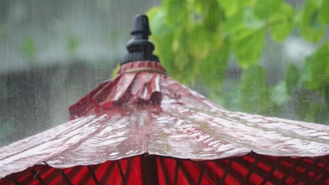 Close up of raindrops bouncing and falling down from old  red paper umbrella on a heavy rainy day,4K video low angle view. Mulberry umbrella,art and crafts product of Thailand.