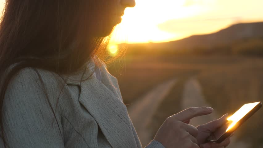 deushka's fingers guide their fingers across tablet. businesswoman checks email. Business woman working on tablet at sunset in park. Agronomist working with tablet in field.