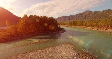 4k (UHD) aerial view. Low flight over fresh cold mountain river at cloudy summer morning. Green trees and sun rays on horisont. Fast horizontal movement