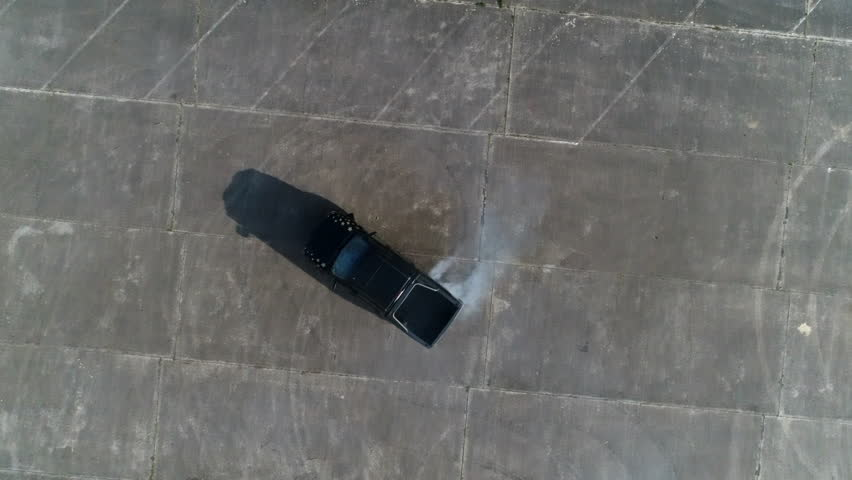 AERIAL: Topshot of a black truck doing donuts on an abandoned parking lot. | Shutterstock HD Video #1028289251