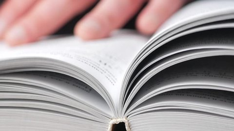Person turning the page of a book up close. read a book