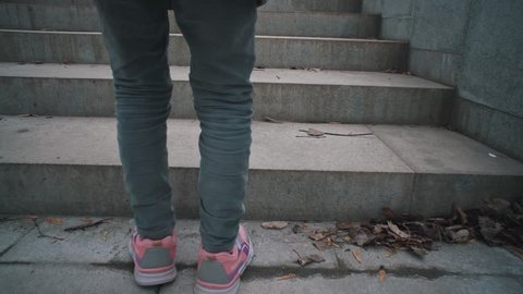View back camera follow of little girl in pink sneakers climbs stone steps in dry leaves. Child walks on gray stairways in city park.