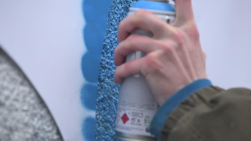 Graffiti artist in the street making art using spray paint and stencil. Stencil street art, urban culture