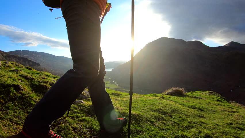 Wales UK - November 2018: Fit Caucasian European woman adventure hiker on her trekking expedition wilderness sun flare #1028325311