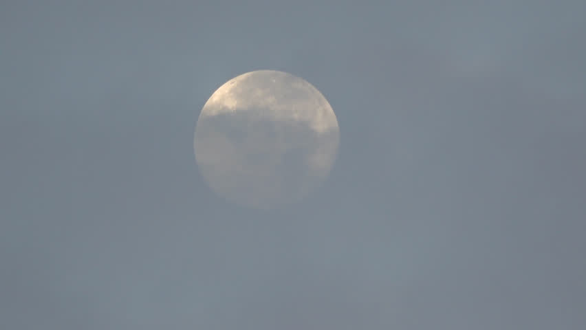 Full Moon Partially Obscured By Thin Clouds During Daylight
