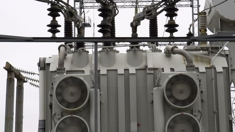 Electrical transformer substation. Power transformer at a power station. Fan cooling power transformer. High voltage transmission power line.