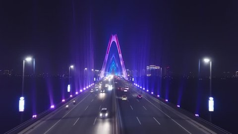 Low span forward inside bridge between pylons Cable-stayed Modern Nhat Tan. Road traffic cars. Beautiful multicolored night neon illumination. Hanoi Vietnam Asia. Travel logistics. Aerial Drone