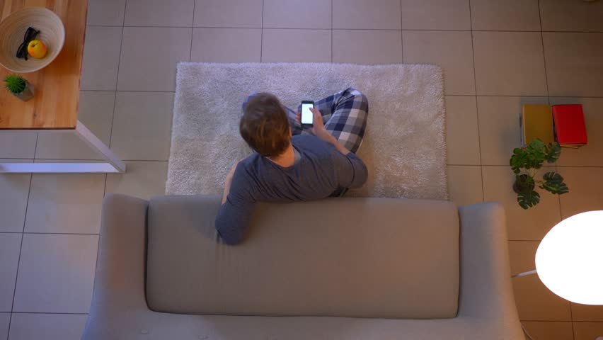 Closeup top shoot of young caucasian male watching TV sitting on the floor and using an app on the phone as a remote control indoors at cozy home | Shutterstock HD Video #1028350601
