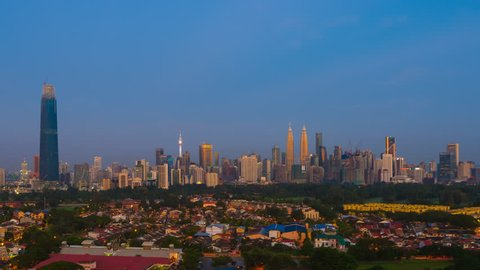 Time lapse : Beautiful and dramatic sunrise view of Kuala Lumpur city skyline from afar and high angle in Malaysia at first light. Zoom out motion timelapse.