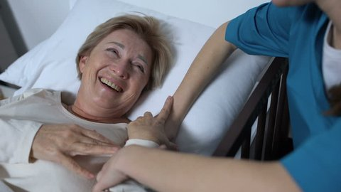 Caring nurse telling jokes to old female patient lying in sickbed rehabilitation