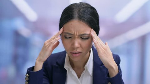 Overworked business woman feeling headache, taking pill with water, health
