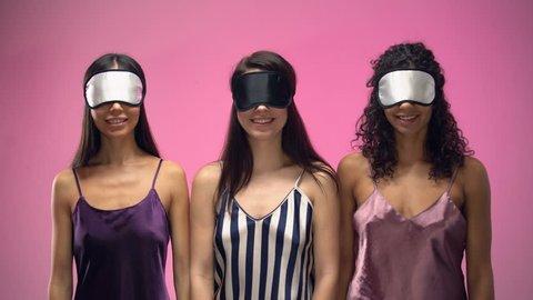 Positive women in pajamas taking off eye masks after waking up, good morning