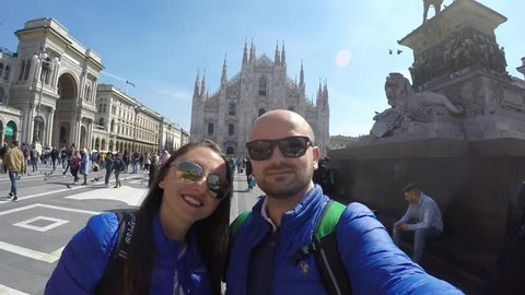 Milan, Italy, April 2019: Young Couple Taking a Selfie at Duomo Cathedral Milano Italy; Happy Family Taking Selfie at Duomo di Milano Waving at Camera; Happy Smiling Tourists at Duomo Milan Cathedral