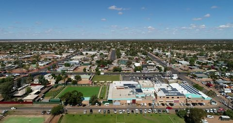 Flat plain around Lightning ridge opal mines town in regional remote NSW seen from above – elevated aerial flying over town streets.