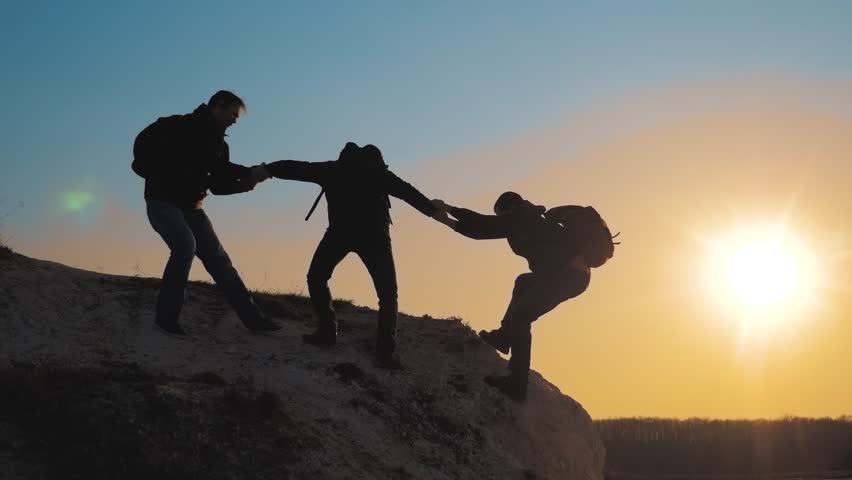 teamwork help lifestyle business travel silhouette concept. group of tourists lends a helping hand climb the cliffs mountains. people climbers climb to the top overcoming hardships the path to victory #1028438561