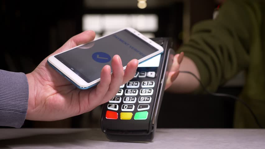 Close-up shot of man applies smartphone to terminal performing successful contactless payment. | Shutterstock HD Video #1028450231