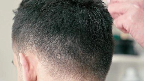 Female Barber is Working and Cutting Hair by Clipper on Back of Head of Young Caucasian Brown-haired Man in Hairdressing or Barbershop Salon. Close Up Slow Motion 4K shot Backside view