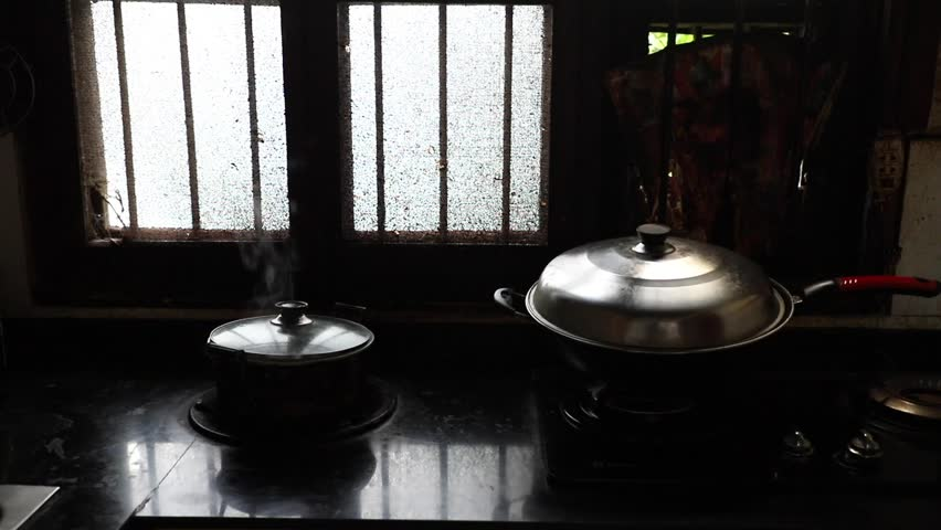 steam rising from pot with boiling water steaming food in old dirty dark kitchen of a village family, Hunan, China