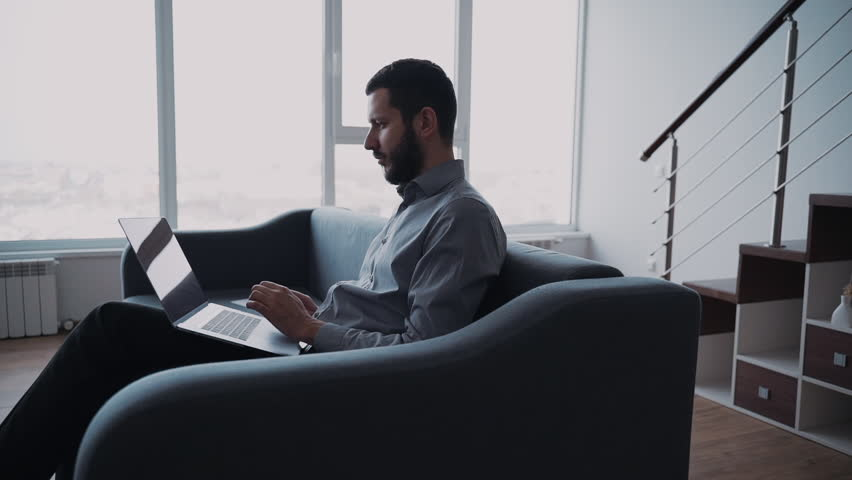 Concentrated, focused and busy man in formal wear clothes sitting on cozy and comfort couch in bright apartment with light interior room. Confident male using laptop and spending free time at home   Shutterstock HD Video #1028461991