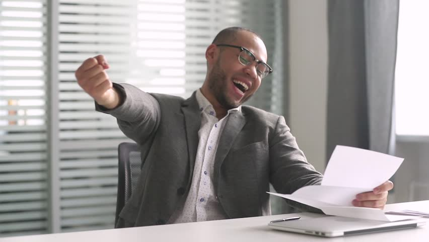 Happy african american businessman winner open envelope read mail letter excited by good news got new job hired promoted, overjoyed by loan approval, receiving bill salary celebrating taxes refund