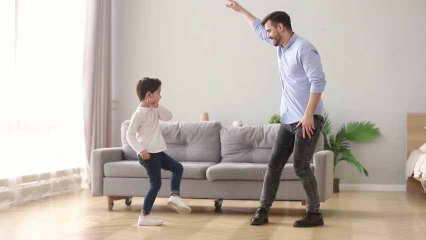 Happy young dad and cute little kid son dancing having fun in living room together, funny active small boy laughing imitating father moving to music, daddy child playing at home on weekend leisure #1028497871