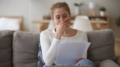 Sad woman sitting on couch at home reads received bad news holds documents paper letter feels desperate about financial problems, domestic bills or debt, girl student worried college expulsion concept