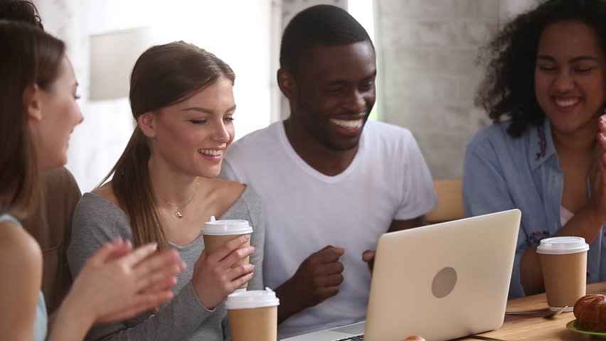 Multiracial friends hang out in cafe drink coffee use computer looking comedy film online laughing, listens music watch video clip move feels overjoyed, generation have fun amusing on internet concept | Shutterstock HD Video #1028517191