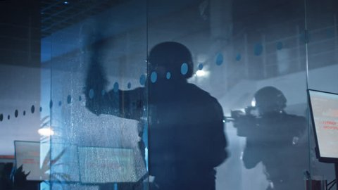 Masked Squad of Armed SWAT Police Officers Storm a Dark Seized Office Building with Desks and Computers. Soldier Breaks a Glass with His Arm and Team Continue to Move. Warm Color Grade.
