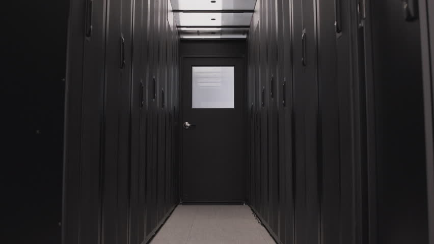 Dark corridor in server room of data center with cloud digital storage. Mining farm and internet information technology concept, no people around. Computer routers in racks on the rows isolated | Shutterstock HD Video #1028554391
