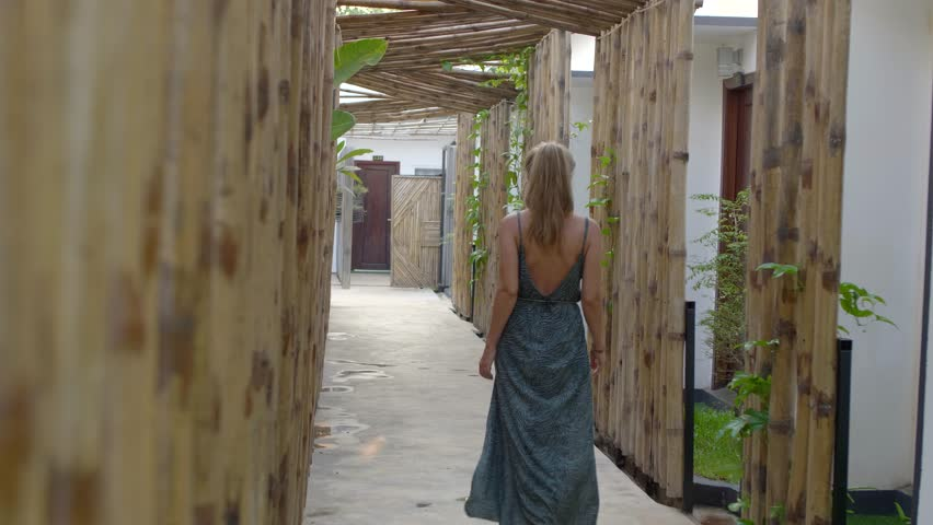 Closeup handheld shot of young beautiful girl in a dress walking along bamboo decorated hall or fence in a luxury asian hotel hall at sunset.Travel,adventure,destination concept, #1028572091