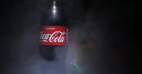Baku, Azerbaijan - APRIL 20. 2018, Coca-Cola Classic in plastic bottle on dark toned foggy Background. Coca Cola, Coke is the most popular carbonated soft drink beverages sold around the world