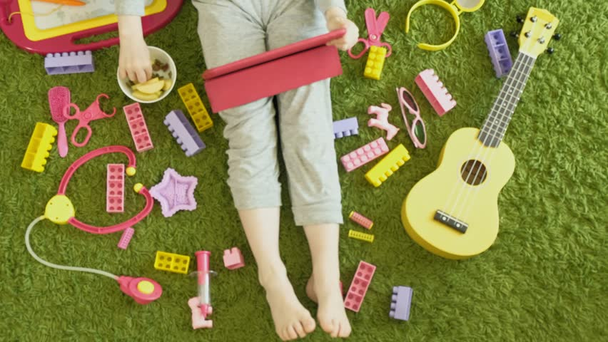 Beautiful little girl with red hair in gray pajamas sitting on the floor using a computer tablet, watching a video or playing and laughing, lying around toys of yellow, pink and purple, top view | Shutterstock HD Video #1028588831