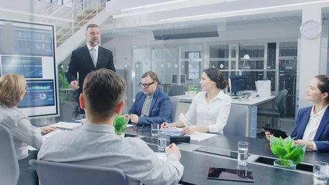 In the Corporate Meeting Room: Enthusiastic Director Uses Digital Interactive Whiteboard for Presentation and Delivers Powerful Speech to a Board of Executives. Everybody Cheers and Applauds