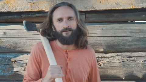 Masculin bearded long hair man in orange longsleeve with an ax try looks to the camera. Male power in the Belarusian village. Hard working. Authentic life. Old Believers. Yoga teacher