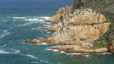 High rock face cliffs with ocean waves breaking on rocks, with white foam covered deep blue sea river mouth, high angle view, natural beauty scene, sunny, Knysna, South Africa