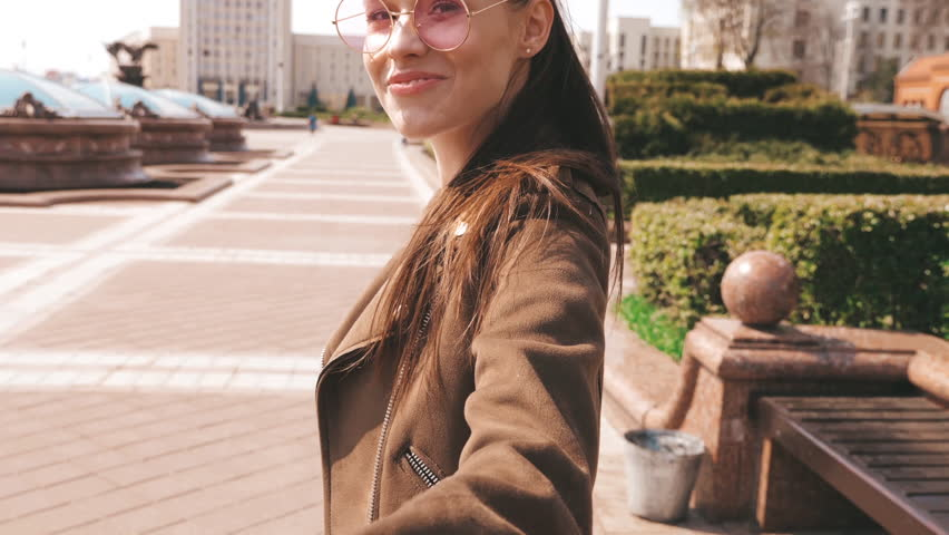 Back view.Follow me romantic concept. Young woman with long hair holding her boyfriend's hand. Smiling girl running in the city. Turning around in sunglasses. Having fun and going crazy. Slow motion | Shutterstock HD Video #1028726141