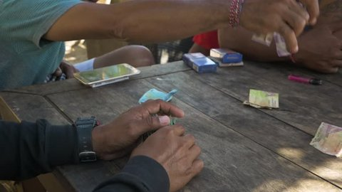 Seminyak, Bali / Indonesia - 08 23 2018: Balinese collects money after winning in a card game. Seminyak Bali Indonesia. Close up August, 2018